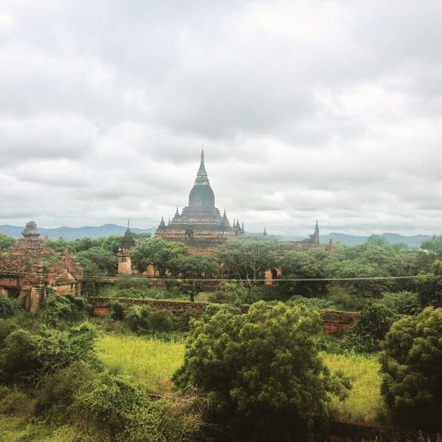 green field with ancient temples, Bagan, Myanmar