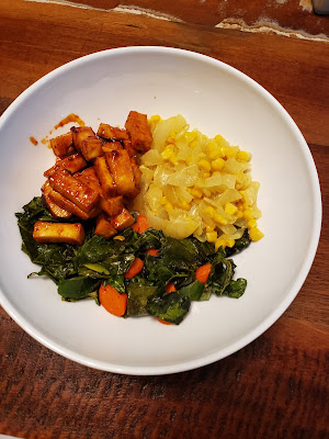 A dish of BBQ tofu, creamed corn, and collard greens with carrots