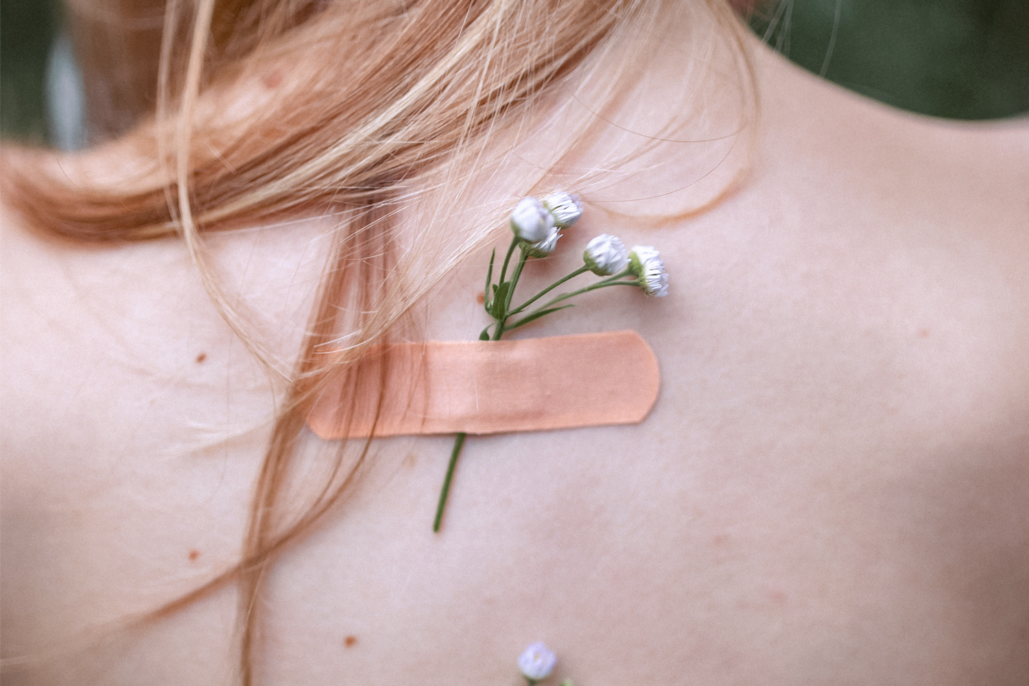 a band aid taped to womans back with a flower underneath it