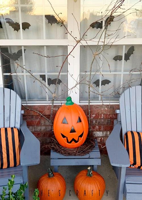 Halloween porch decor - branches, pumpkin, adirondack chairs