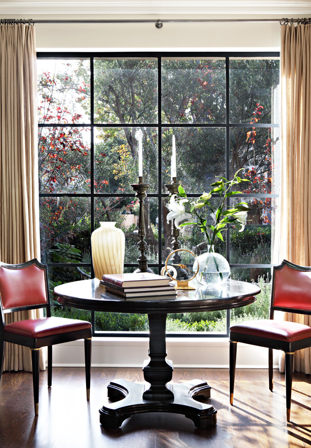 Round table and chairs at large black steel framed window in a living space with interior design by Kazuko Hoshino and architecture by William Hefner. This is their own Provence style home in LA. #classicdecor #Frenchcountry #Provence