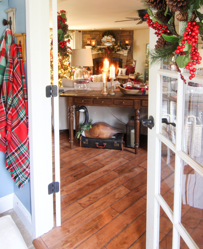 Family room with stone fireplace and classic plaid Christmas decor -www.goldenboysandme.com
