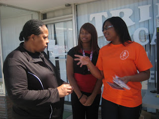 SHSU Students Veronica and Jessica Stubblefield (center and right, respectively) talk to a resident outside the Trinty Cafe about child safety gun locks as part of a community service project.