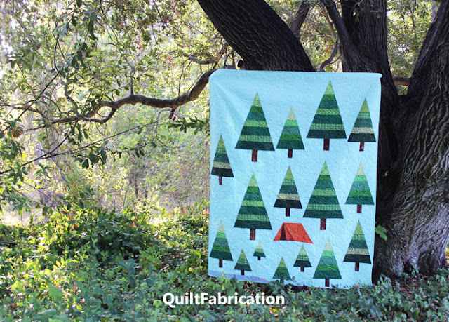 camping quilt of green trees and an orange tent held up next to a tree in the great outdoors by QuiltFabrication
