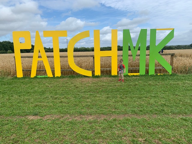 Patch MK signage, with little boy running