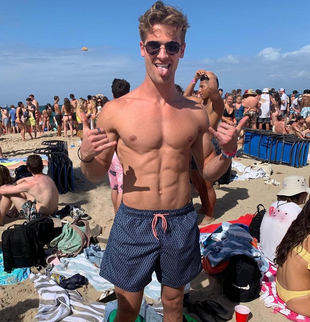 attractive-barechest-slim-fit-frat-college-boy-sunglasses-beach-sand-crowd