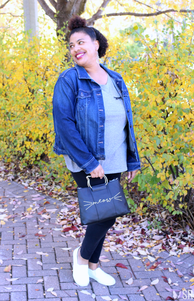 a woman walking outside in the fall leaves with a jean jacket and eyelash tshirt