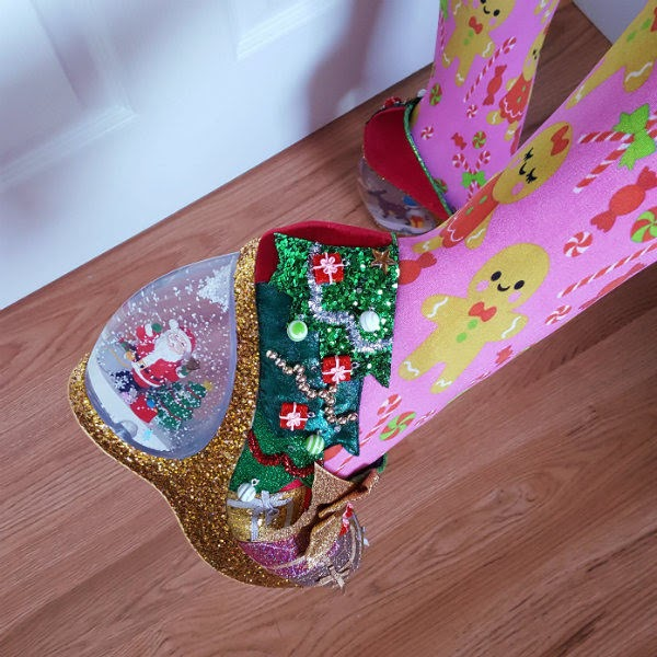 close up of Christmas shoe on foot showing Santa inside snowglobe heel with snow and snowflakes floating