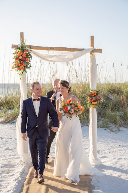 Bride and groom walking down beach aisle with floral alter.