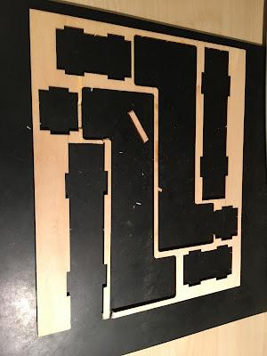 Auf einer schwarzen Gummimatte liegt der hellbraune Holzrahmen bei dem die Teile entnommen sind.