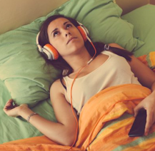 A caucasian woman with brown hair wearing a white top laid in bed listening through some headphones. The bedding is orange and green.