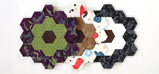 English paper piecing hexagon flower blocks 27, 28, and 29 lined up on a white background.