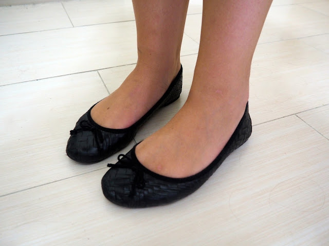 Inverted   outfit shoe details of flat black ballet pumps, with leather effect print and bow details
