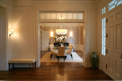 Entry with walnut flooring and view of dining room in traditional home designed by Steve Giannetti