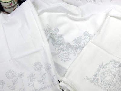 Three flour sack towels designed by Mary Corbet ready to stitch