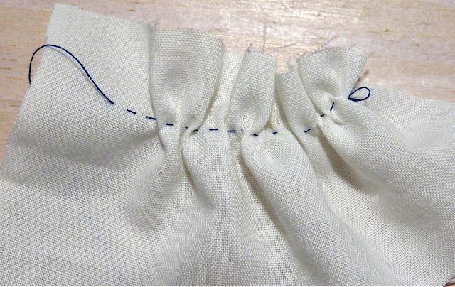 Punto bastilla o cómo fruncir a mano con hilo azul sobre tela blanca
