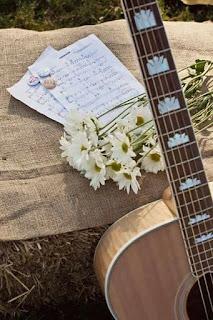 Foto de guitarra, partitura musical y flores