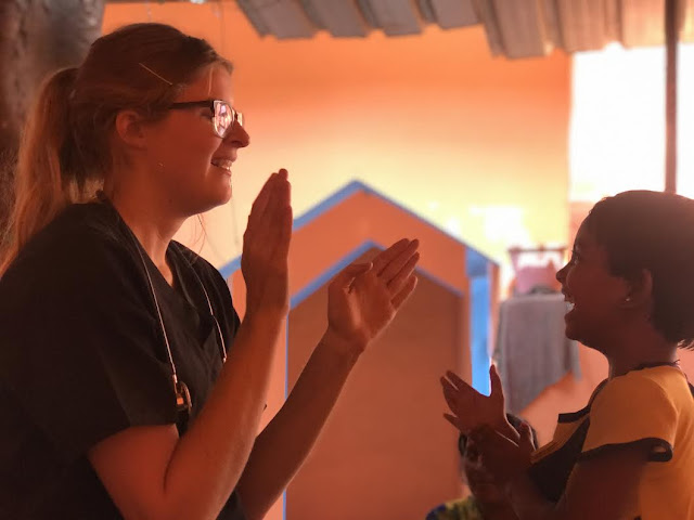 2nd Lt. Samantha Lonergan playing patty cake with a little girl at the New Hope clinic. [Image credit: Courtesy of 2nd Lt. Samantha Lonergan]
