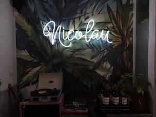 nome Nicolau na parede com papel de parede com plantas e uma vitrola na frente