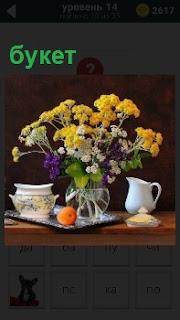 На столе в вазе стоит букет красивых цветов рядом с чашкой и кувшином с водой