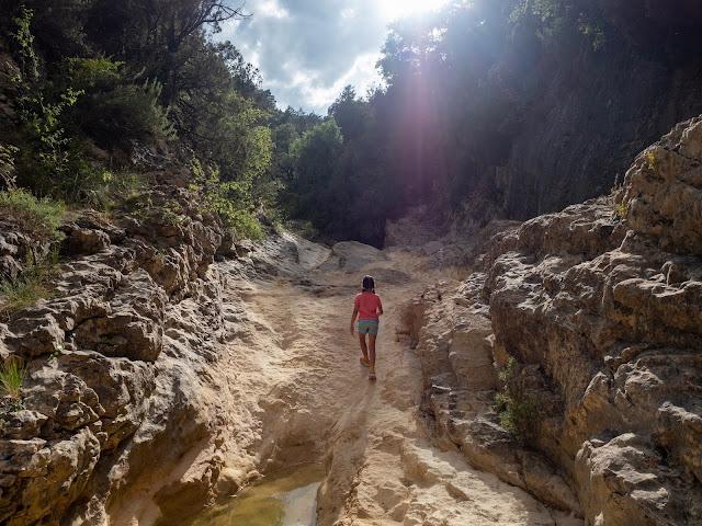 Niña de espaldas co el sol detrás caminando por el lecho del río en las pozas de San Martín (Huesca)