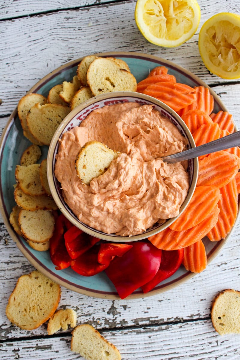 Top view of Smoked Salmon Dip in a tan bowl on a blue plate with bagel chips, carrot chips, and bell pepper pieces around it.