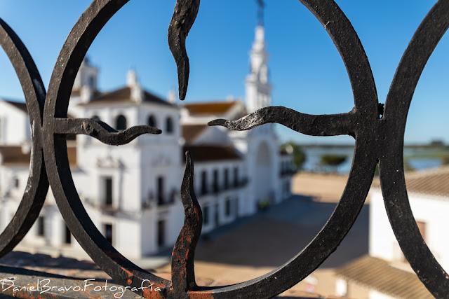 Vista lateral de la Ermita de El Rocío desde una azotea cercana, a través de la decoración de una barandilla.