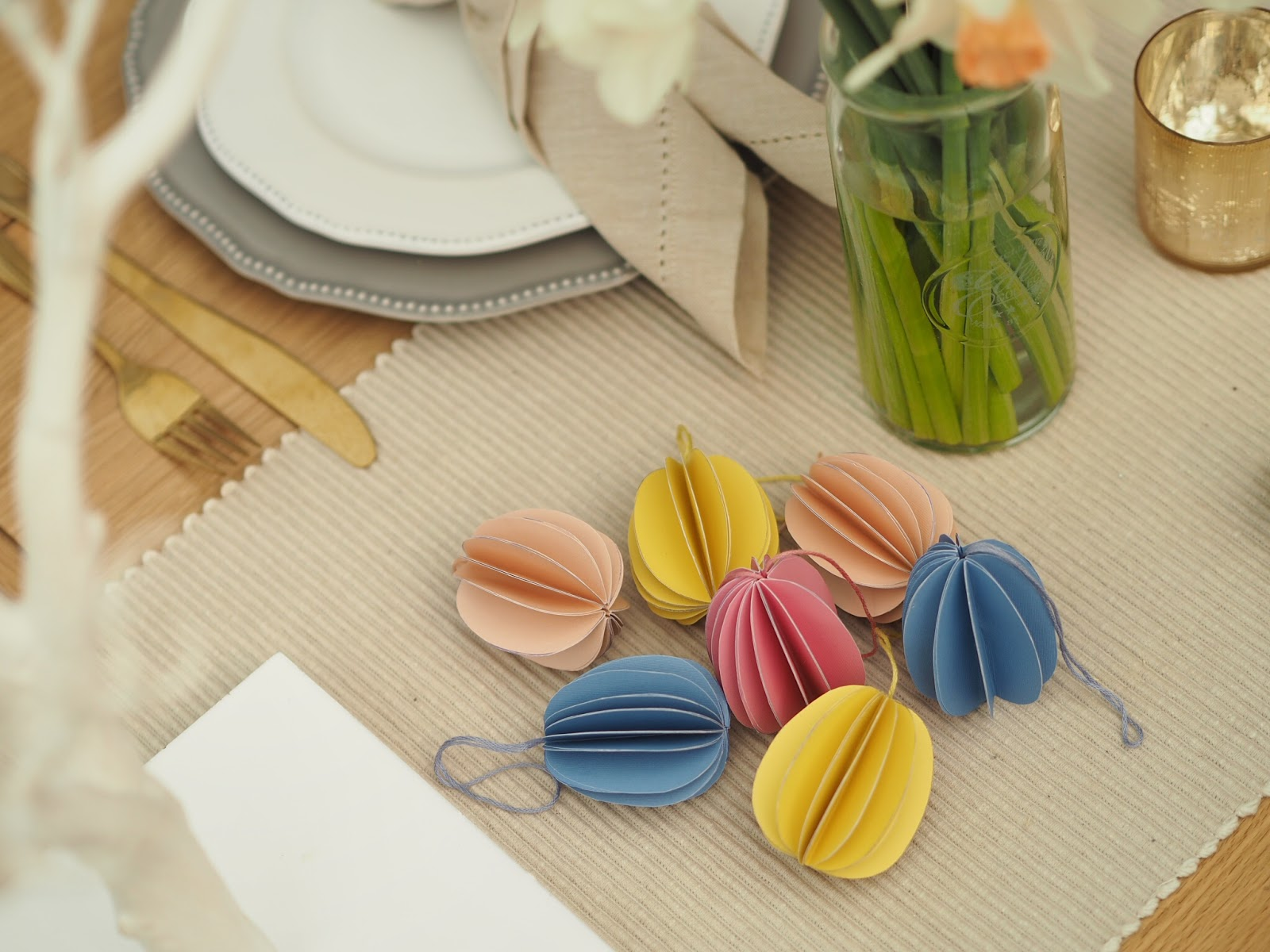 How to make Easter paper decorations in the shape of an Easter egg, perfect for decorating your home for spring, or for creating a pretty seasonal table setting. DIY tutorial craft perfect for when you're stuck inside at home on lockdown.
