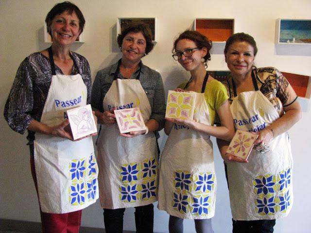 4 mulheres segurando os azueljos que pintaram no workshop
