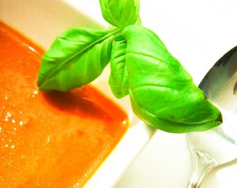 a close up of four tomato and red pepper soup with fresh basil in a white bowl