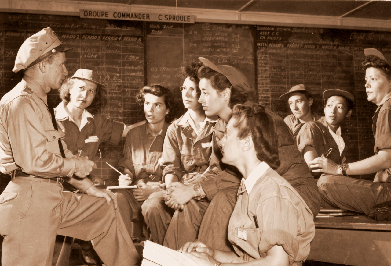 WASPs being briefed in ready-room, Avenger Field, Sweetwater, Texas, May 1943. Front row, l to r: Group Commander Charles M. Sproul, Irma Cleveland, Faith Buchner, Martha Lundy, Mary Jane Stevens, Anabelle Kekic. Back row, l to r: Ruby Mullins, Hazel Ying Lee, Virginia Harris Mullins.