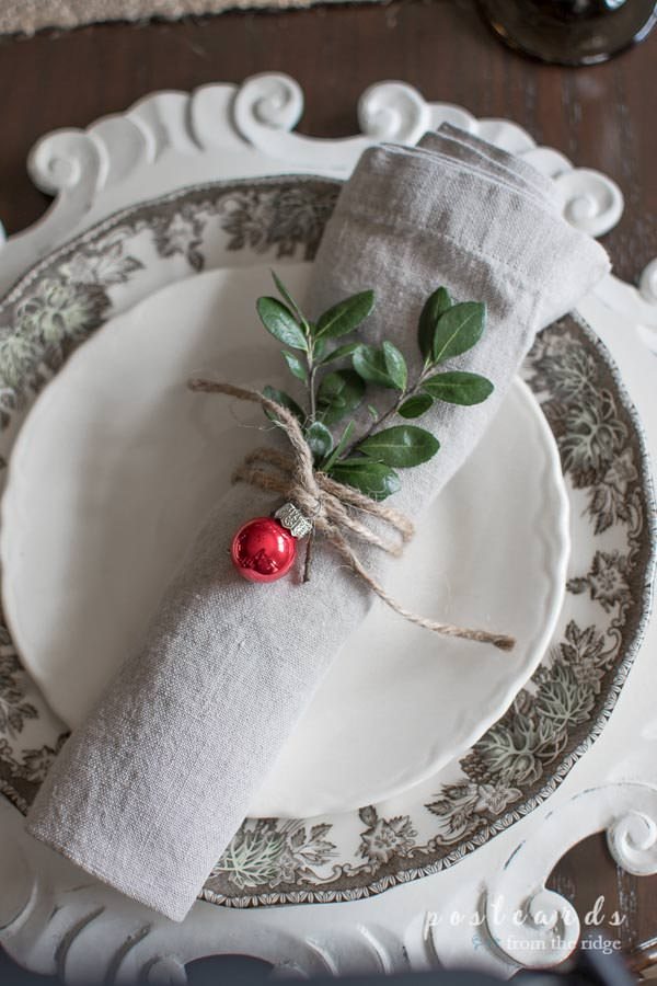 Christmas table setting with linen napkin tied with twine and small red mercury glass ornament