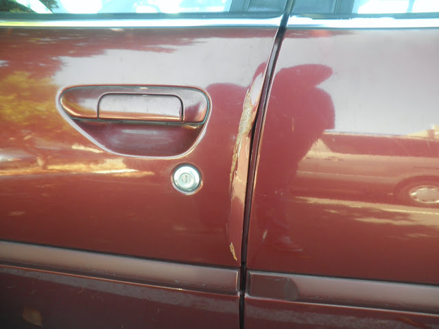 Dented door on 2000 Nissan Altima before collision repairs at Almost Everything Auto Body