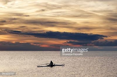 Κωπηλάτης με βάρκα στο πέλαγος. Ακολουθεί το κείμενο: Είναι το πυκνό συλλαλητήριο που οργανώνει μόνος ένας, μόνος, κάπου ένα μαχαίρι είναι που βρέθηκε δίχως ν' ακουστεί κανένας φόνος.  Όπλου είναι βολή χωρίς αντήχηση στη μεγάλην άμμο μιας Σαχάρας, πάνω μια χλωμή λειψή πανσέληνος λιώνει σαν κεράκι της δεκάρας…  Είναι μια σημαία που ξεχάστηκε στον ιστό μετά τη δύση του ηλίου, ξέθωρο ένα ράκος που φυλάχτηκε από εσθήτα περασμένου μεγαλείου.  Έρημος σταθμός το μεσονύχτιο υπογείων αστικών σιδηροδρόμων, πέτρες φορτωμένον είναι φέρετρο που το πάνε τέσσερις στον ώμον.  Βάρκα είναι στο πέλαγο τ' απέραντο μ' ένα σκελετό για κωπηλάτη που ήλιος κατακόρυφος τον στέγνωσε και τον λεύκανε της θάλασσας τ' αλάτι.  Είναι το πουλί που μόνο ξώμεινε μίλια απ' το κυρίαρχο κοπάδι, πίσω του το φως της μέρας σβήνεται