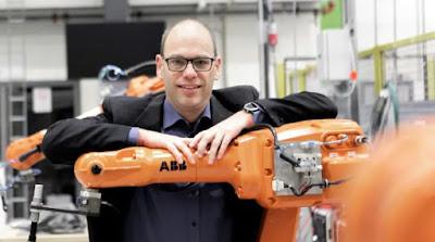 Fredrik Danielsson lutar sig mot en orangefärgad industrirobot.