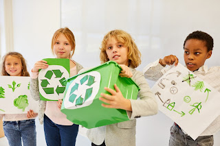 Four youth holding a recycling bin and their drawings for an environmental protection recycling project