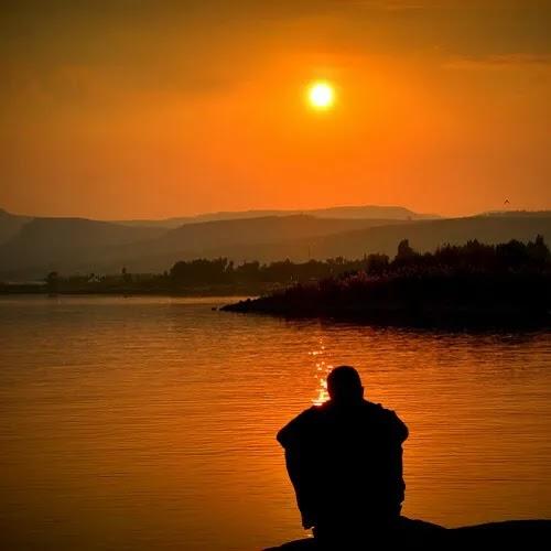 alone boy sitting in evening near river