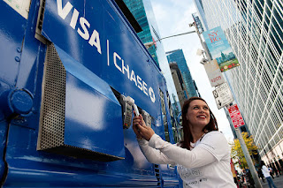 Photo of a woman standing next to a Visa Chase sign.
