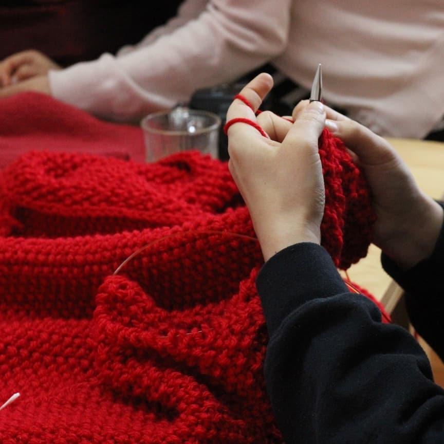 En la foto persona teje a palilo con lana roja
