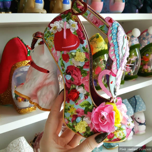 cat heeled floral shoe in hand with shoe shelves in background