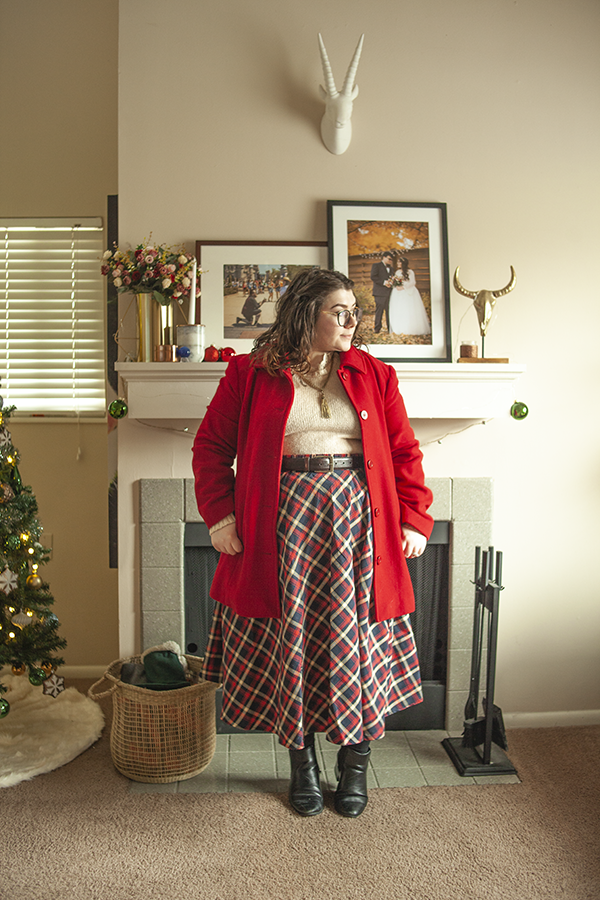 An outfit consisting of a red coat, a cream sweater tucked into a red, navy blue and white plaid long skirt with black heeled Chelsea boots.