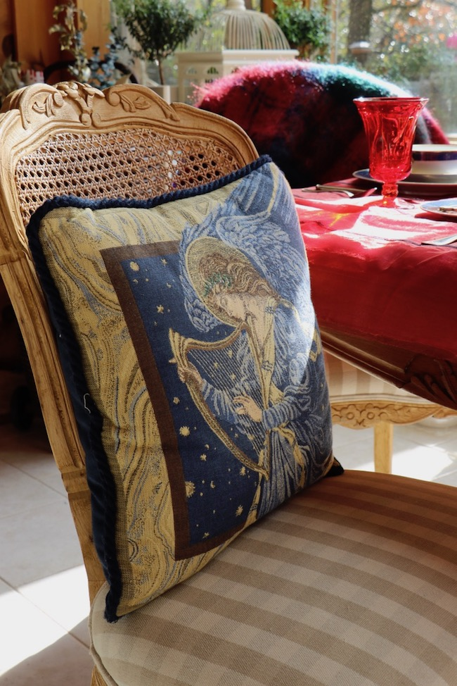 A navy and gold angel pillow sits on a French Country dining chair around the Christmas Red and Navy Blue Table Setting