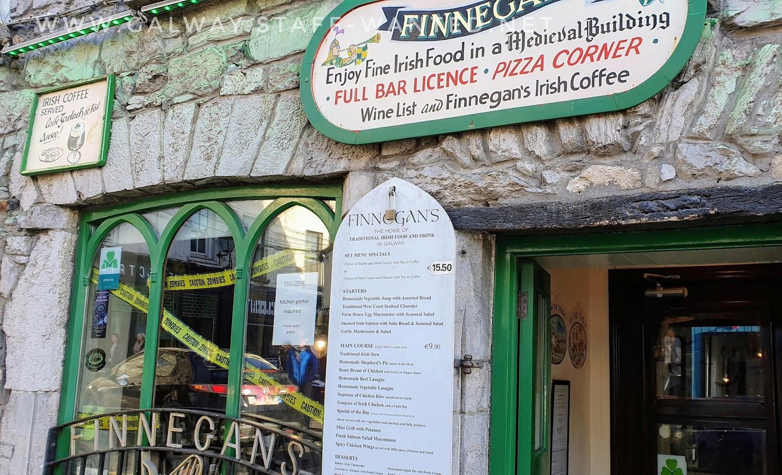 sign in Irish restaurant window with Halloween decorations - and Finnegans restaurant menu board - main €15.50.