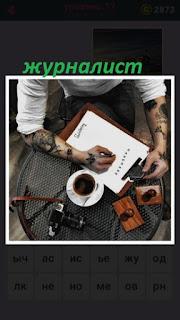 за столом сидит журналист и пишет статью, рядом чашка кофе