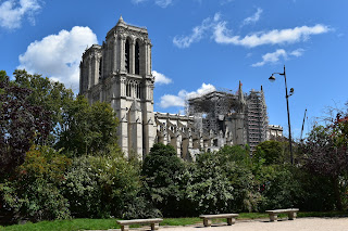 view of Notre Dame Cathedral from a park across the street. Green trees frame the broken structure and scaffolding of the famous site.