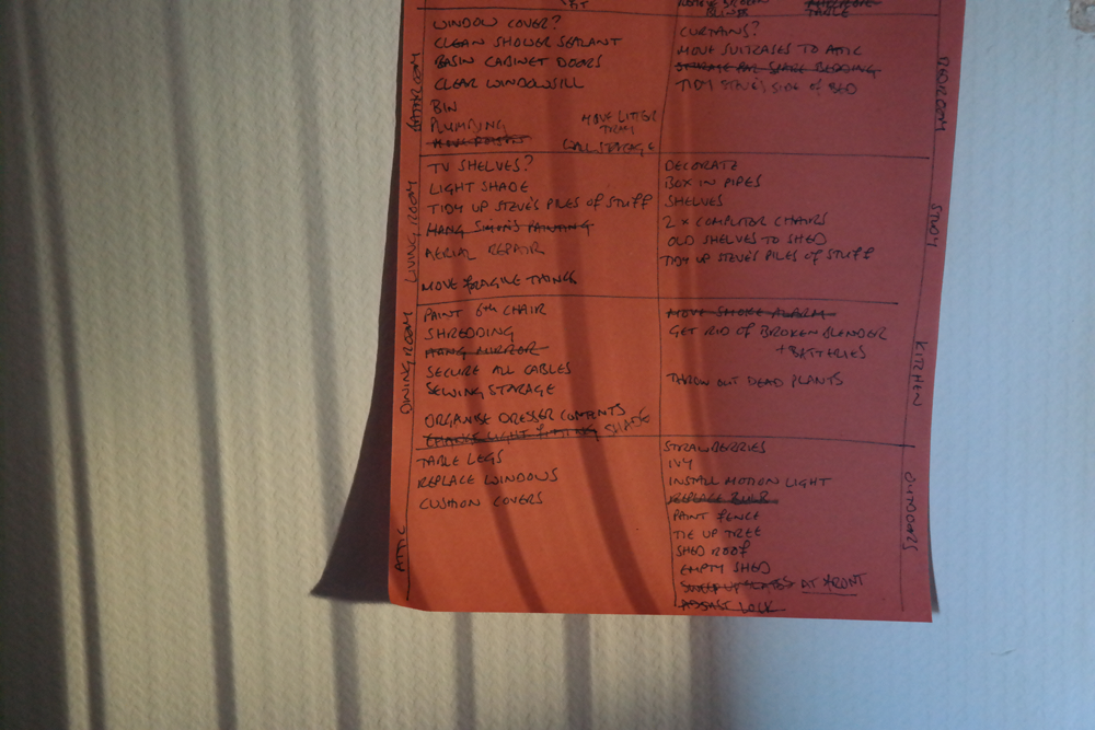 Detailed to do list of DIY jobs written on orange paper. Not all bloggers live in pristine white palaces.
