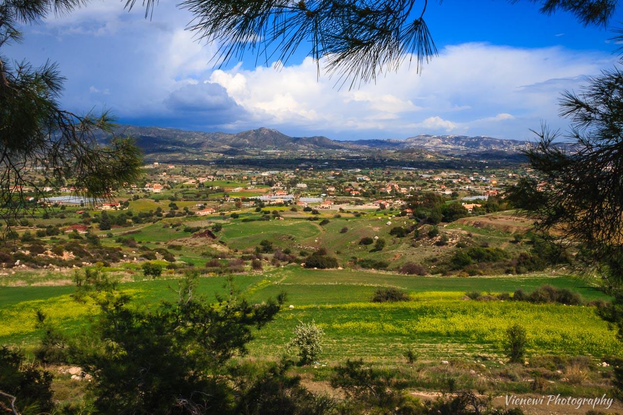 Wiosenny krajobraz w Paraklishia z blękitnym, zachmurzonym niebem i zieloną łąką przyozdobioną żółtymi kwiatami.