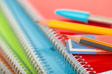 Pile of notepads with pencils, pen and a rubber on top