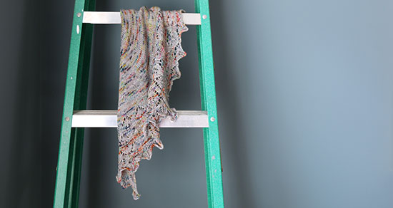 Wool hand knit lace scarf in gray with colorful flecks draped on a metal ladder in front of a blue wall.