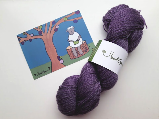Image shows a skein of purple yarn lying on a white background with a postcard of a sheep knitting under a tree
